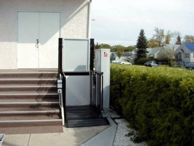 A vertical wheelchair lift installed outside a business